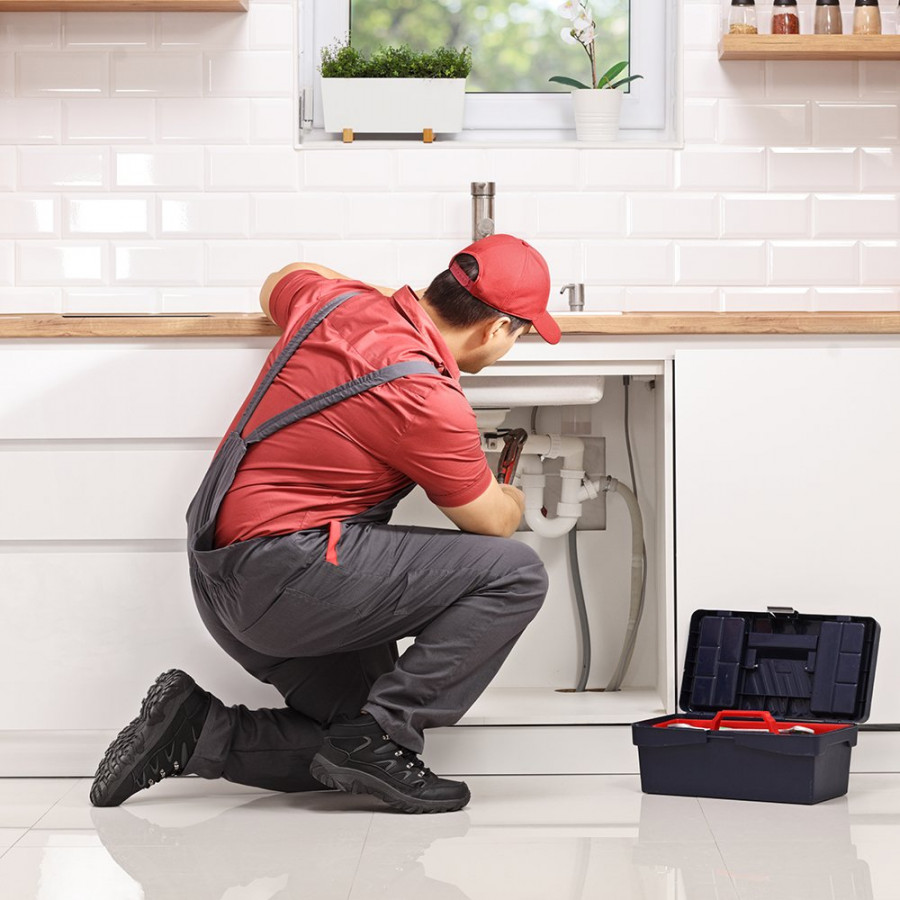 Plumber kneeling and fixing a pipe under sink in a modern kitchen
